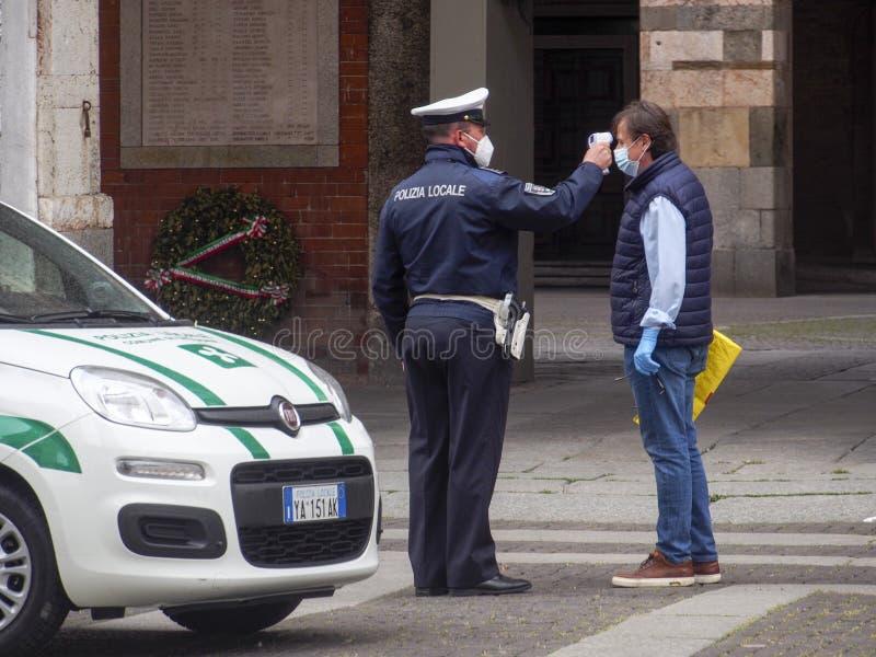 2020年5月13日,意大利伦巴第州克雷莫纳 — 当地警官,测量成年人 人体体温红外测温仪 库存图片