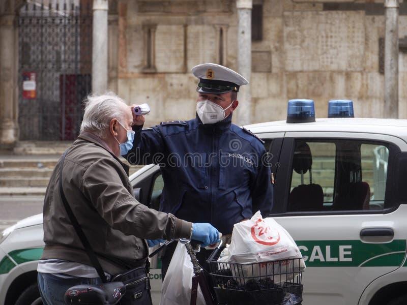 2020年5月13日,意大利伦巴第州克雷莫纳 — 当地警官,测量高级成年人 体温用红外线 免版税图库摄影