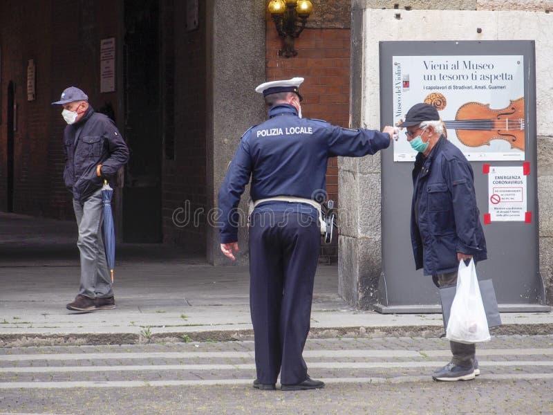2020年5月13日,意大利伦巴第州克雷莫纳 — 当地警官,测量高级成年人 体温用红外线 免版税库存照片