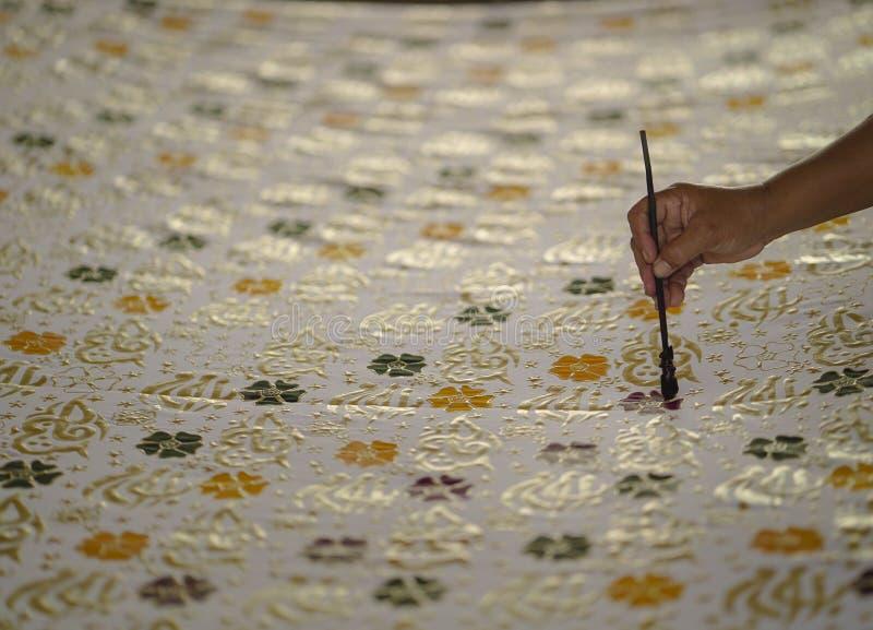 2019年8月11日,苏腊卡尔塔印度尼西亚:做蜡染布的接近的手在与倾斜的织品有bokeh背景 库存照片