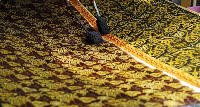 2019年8月11日,苏腊卡尔塔印度尼西亚:做蜡染布的接近的手在与倾斜的织品有bokeh背景 免版税库存照片