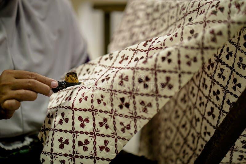 2019年8月11日,苏腊卡尔塔印度尼西亚:做蜡染布的接近的手在与倾斜的织品有bokeh背景 库存图片