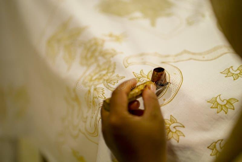 2019年8月11日,苏腊卡尔塔印度尼西亚:做蜡染布的接近的手在与倾斜的织品有bokeh背景 免版税库存图片