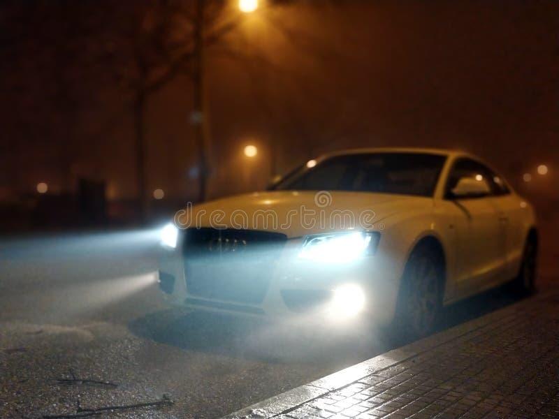 2018年3月1日,-塔拉萨,西班牙-在与薄雾的晚上被射击的白色汽车前面 免版税库存图片