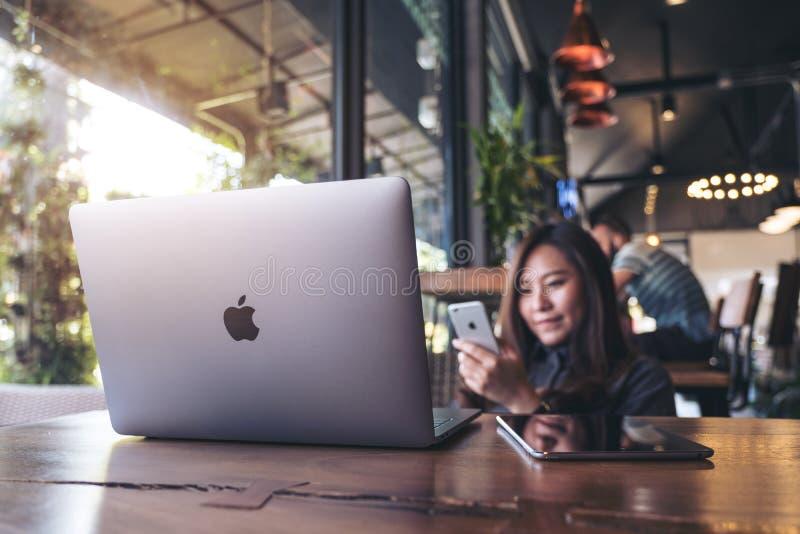 2017年11月17日:拿着有膝上型计算机的亚裔女商人巧妙的电话在现代咖啡馆, Chiangmai泰国的木桌上 免版税库存照片