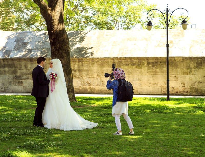 E ?? 2016年5月5日:摄影师在公园拍一对美好的回教婚姻的夫妇的照片 免版税库存照片