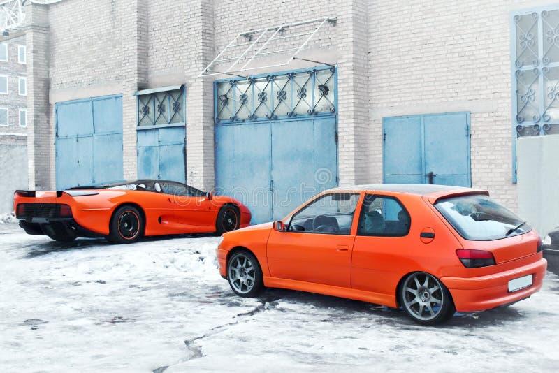 2013年1月3日;基辅,乌克兰 捷豹汽车XJ220 1991年和小标致汽车 免版税图库摄影