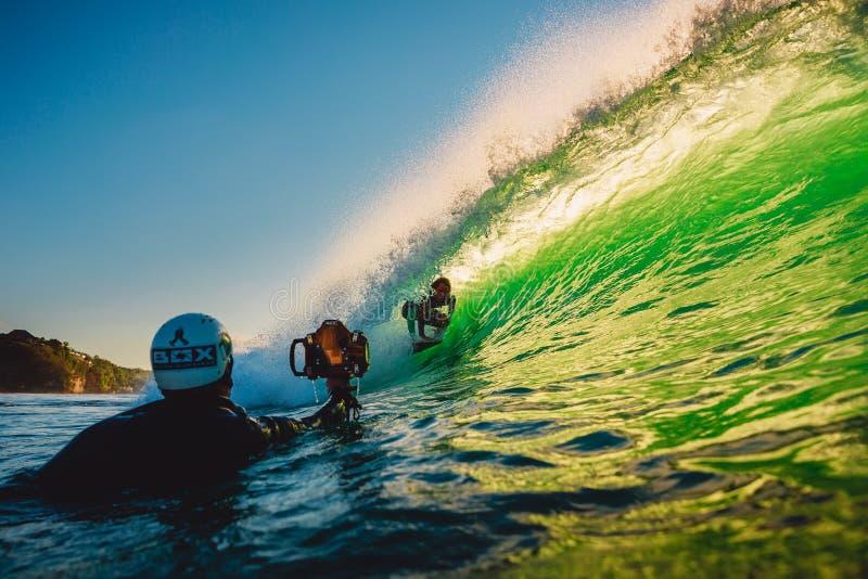 2018年9月8日 巴厘岛印度尼西亚 在桶波浪和海浪摄影师的冲浪者乘驾日落的 专业冲浪在海洋 库存图片