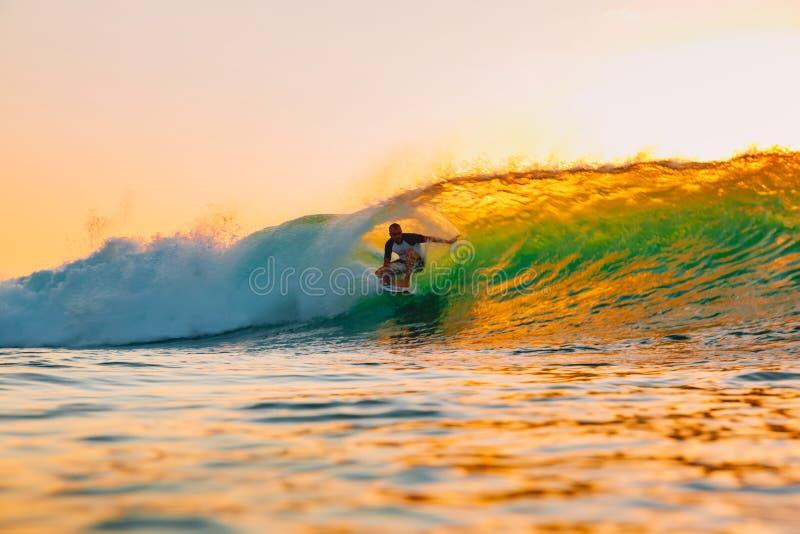 2018年9月8日 巴厘岛印度尼西亚 在桶波浪的冲浪者乘驾在温暖的日落 专业冲浪在海洋,Bingin海滩 免版税库存照片