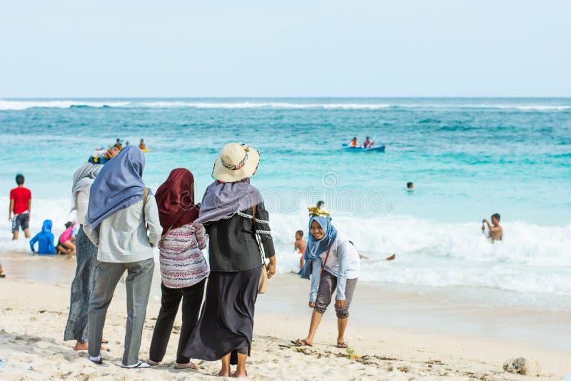 2017年12月28日-巴厘岛,印度尼西亚:站立在海滩的小组回教妇女在巴厘岛印度尼西亚 免版税库存图片