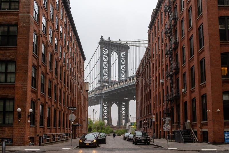 2019年5月04日-美国,纽约:从在布鲁克林街道的红砖大厦看见的曼哈顿桥梁在透视 免版税库存图片