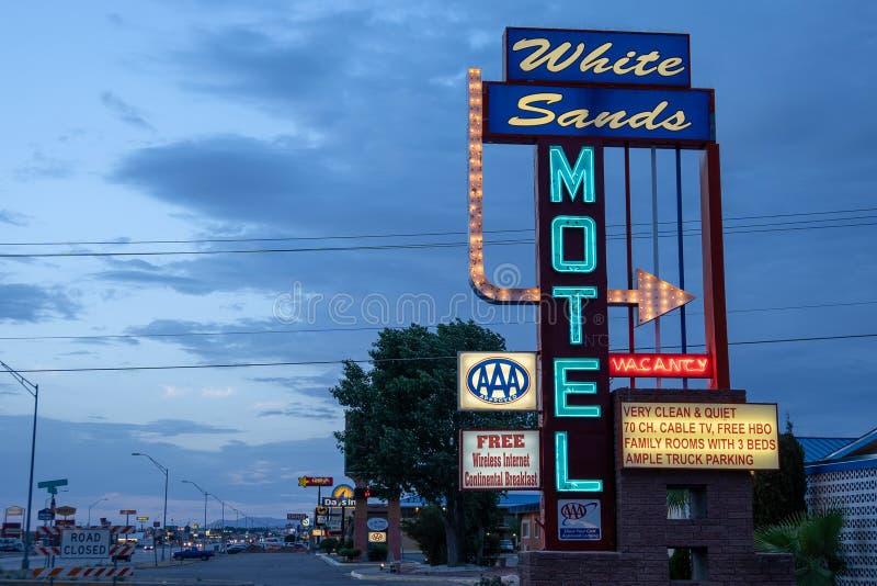 2018年6月30日- ALAMOGORDO,新墨西哥:减速火箭的样式白色铺沙汽车旅馆照亮在黄昏蓝色小时 免版税库存图片