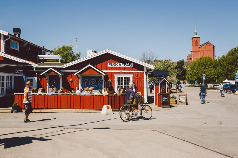 2014年4月17日 nynashamn城市在瑞典 波罗的海的堤防 与大阳台的木咖啡馆红色 人们吃着得外面 库存照片