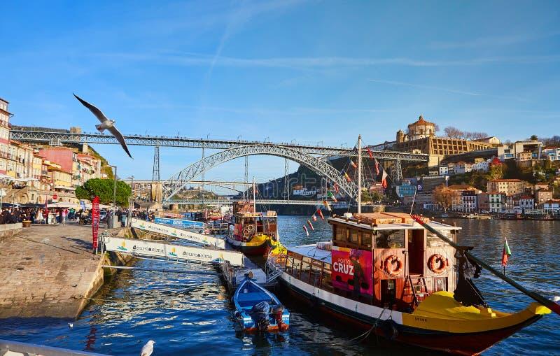 09 2018年12月-波尔图,葡萄牙:有葡萄酒桶的传统小船在杜罗河河在老镇有Dom雷斯背景  免版税图库摄影