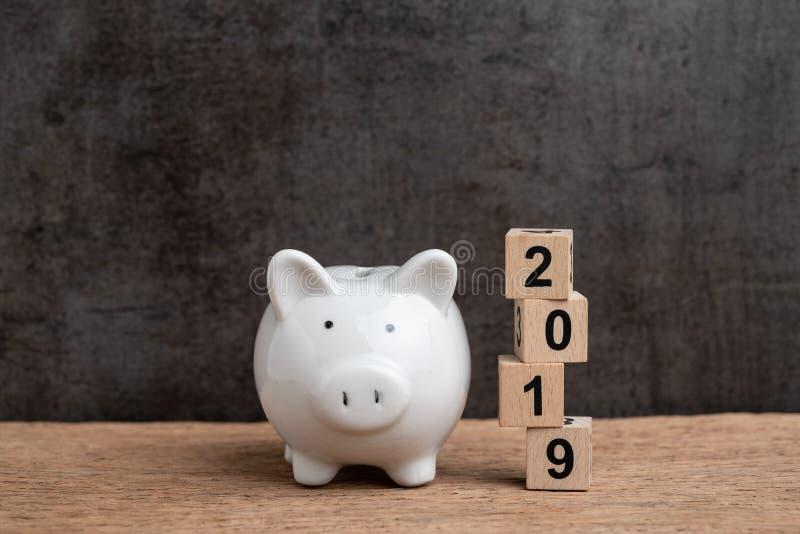 年2019财政目标、预算、投资或者企业目标概念、白色存钱罐和堆立方体木块大厦 免版税库存图片