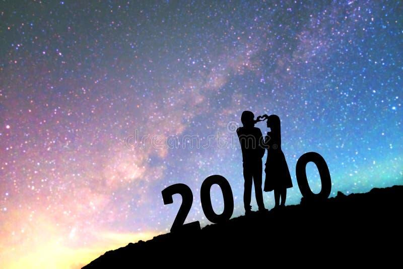 2020年Newyear现出轮廓年轻夫妇愉快为在指向在一个明亮的星的银河星系的浪漫背景 免版税库存图片