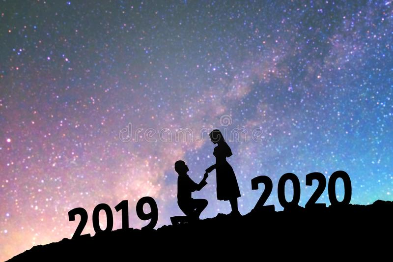 2020年Newyear现出轮廓年轻夫妇愉快为在指向在一个明亮的星的银河星系的浪漫背景 免版税库存照片