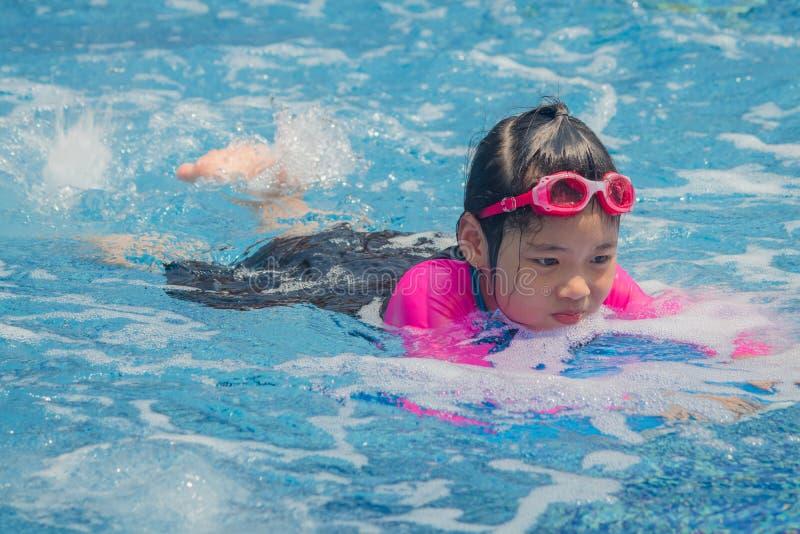 幸福亚裔逗人喜爱的女孩在游泳场有滑稽的感觉并且享用 免版税库存图片