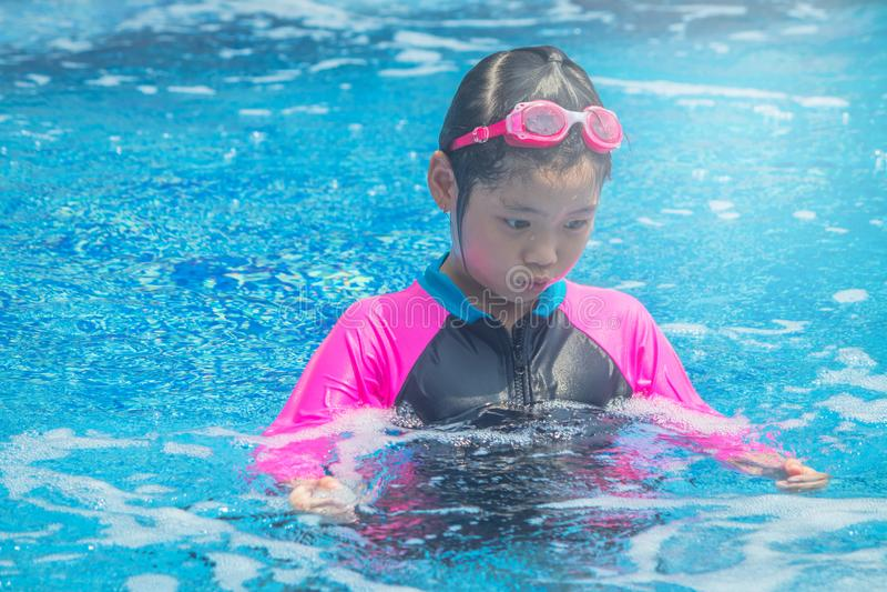 幸福亚裔逗人喜爱的女孩在游泳场有滑稽的感觉并且享用 库存照片