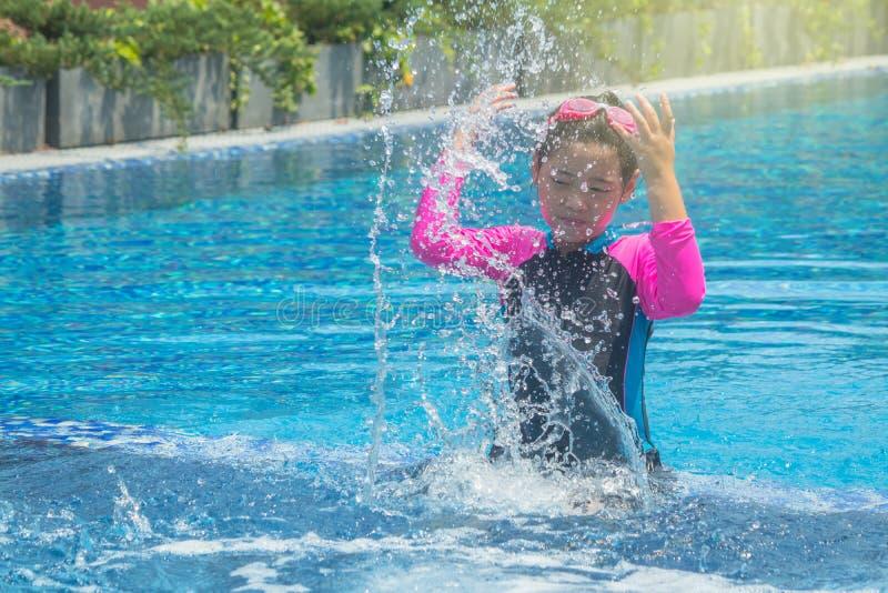 幸福亚裔逗人喜爱的女孩在游泳场有滑稽的感觉并且享用 库存图片