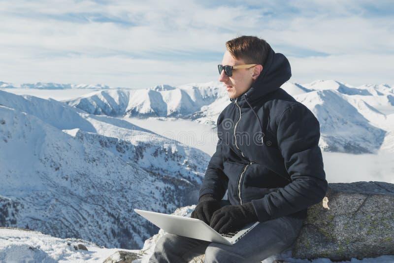 幸福到极点研究膝上型计算机的年轻商人自由职业者画象  冬天lanscape在晴天 图库摄影