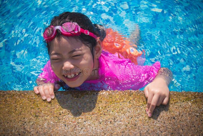 幸福和微笑的亚裔逗人喜爱的女孩在游泳场有滑稽的感觉并且享用 免版税库存图片
