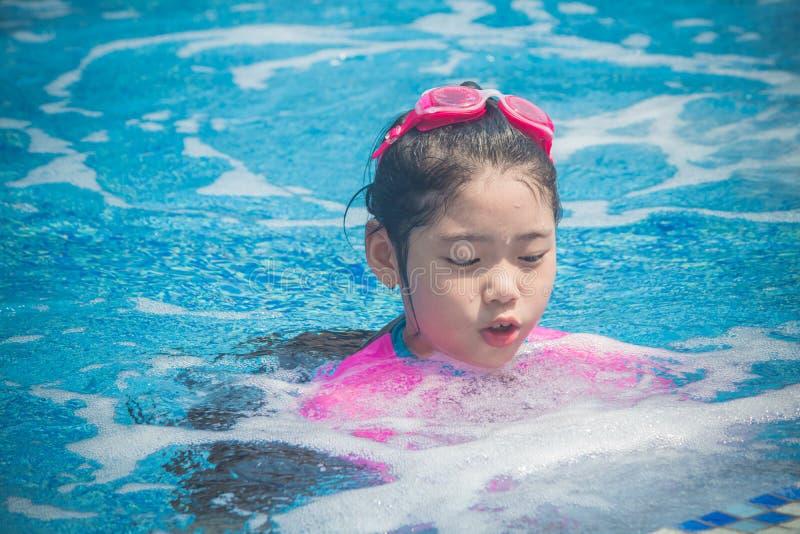 幸福和微笑的亚裔逗人喜爱的女孩在游泳场有滑稽的感觉并且享用 图库摄影