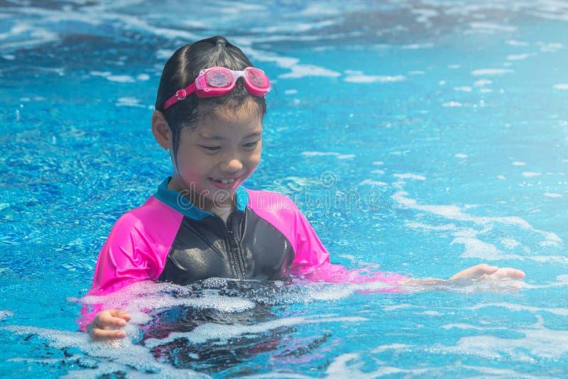幸福和微笑的亚裔逗人喜爱的女孩在游泳场有滑稽的感觉并且享用 库存照片
