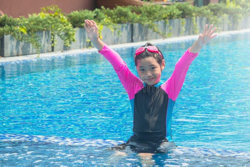 幸福和微笑的亚裔逗人喜爱的女孩在游泳场有滑稽的感觉并且享用 免版税图库摄影