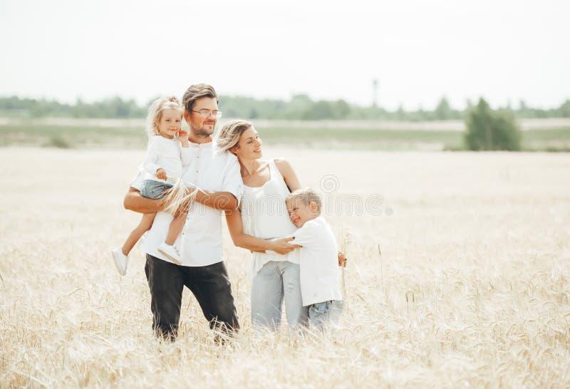 幸福家庭、父亲、妈妈、儿子和女孩麦田的在夏日 库存图片