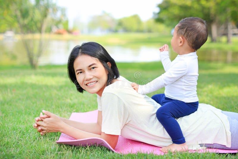 幸福家庭亚裔说谎在绿色草坪背景的妈妈和她的儿子 免版税库存照片