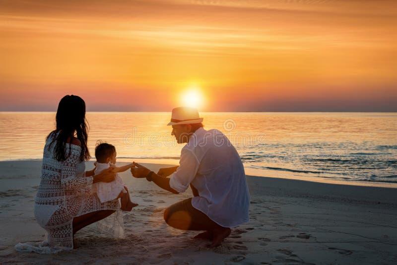 幸福家庭享受在海滩的日落 免版税图库摄影