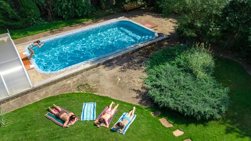 幸福家庭从上面放松由游泳场的,空中寄生虫视图父母和孩子获得乐趣在度假,家庭周末 库存图片