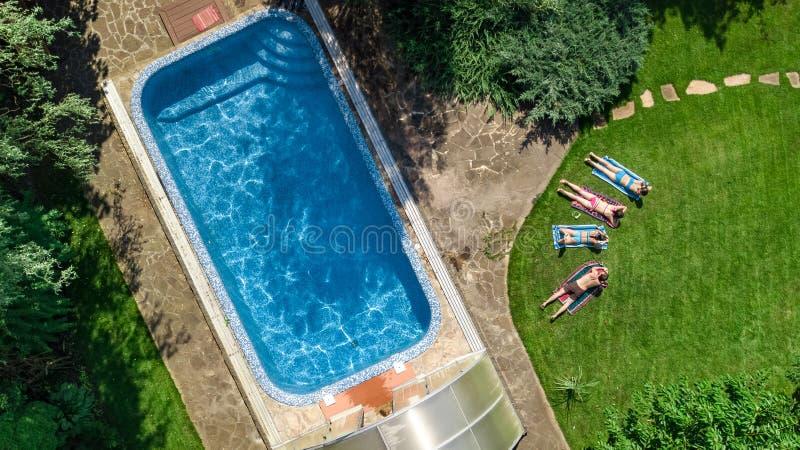 幸福家庭从上面放松由游泳场的,空中寄生虫视图父母和孩子获得乐趣在度假,家庭周末 图库摄影