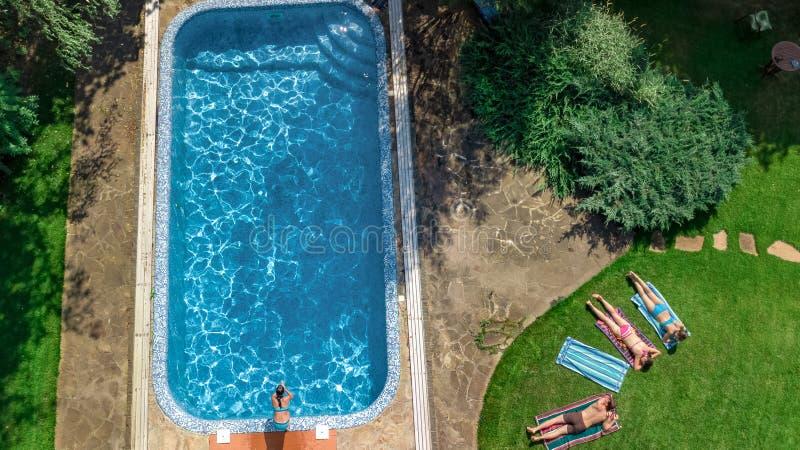 幸福家庭从上面放松由游泳场的,空中寄生虫视图父母和孩子获得乐趣在度假,家庭周末 免版税库存照片