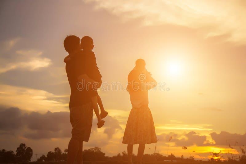幸福家庭使用户外在日落的父亲母亲和儿子 库存图片