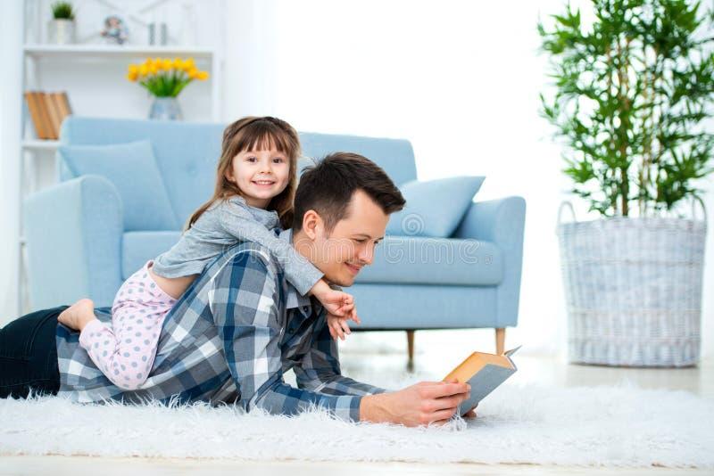 幸福家庭和父亲节概念 有女儿消费时间统一性的爸爸在家 爸爸的后面lyin的逗人喜爱的女孩 图库摄影