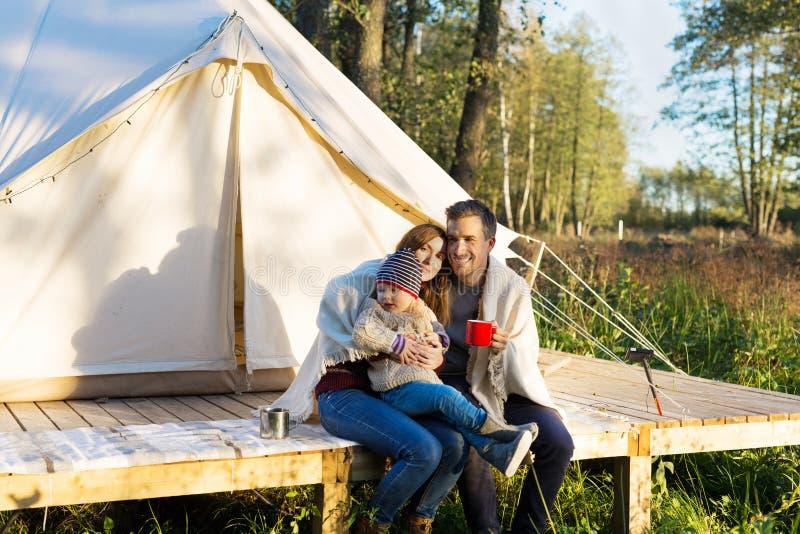 幸福家庭在森林时包裹一揽子在他们自己,当坐在帆布帐篷附近 免版税库存图片