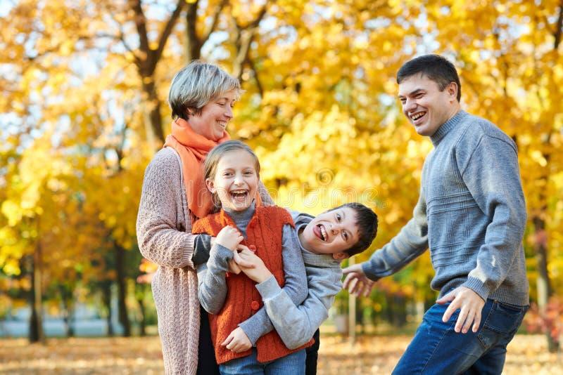 幸福家庭在秋天城市公园走 获得的孩子和的父母摆在,微笑,演奏和乐趣 明亮的黄色树 免版税库存照片