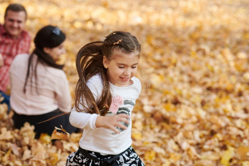 幸福家庭在秋天城市公园 子项和父项 他们摆在,微笑,演奏和获得乐趣 明亮的黄色树 库存照片