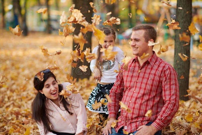 幸福家庭在秋天城市公园 子项和父项 他们摆在,微笑,演奏和获得乐趣 明亮的黄色树 库存图片
