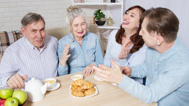 幸福家庭在老人院的茶时间的老人 有孩子的父母有乐趣谈话通信和休闲 高级夫妇 免版税库存照片