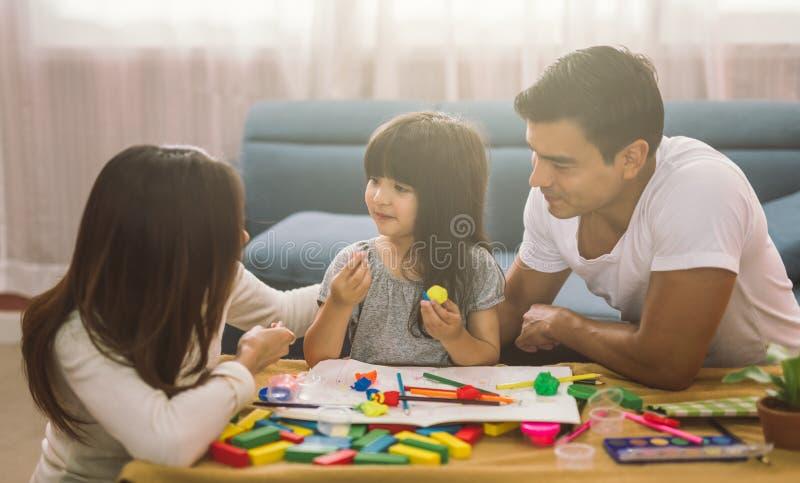 幸福家庭女儿女孩画象学会与父母一起用五颜六色的戏剧面团 免版税图库摄影