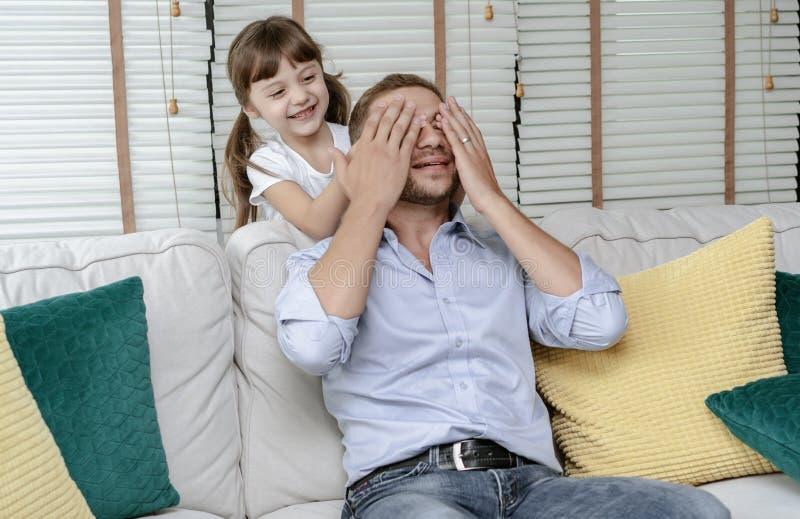 幸福家庭女儿盖她的爸爸眼睛,当使用在度假在客厅时 免版税库存照片