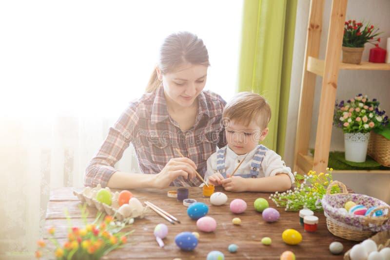 幸福家庭妈妈和儿童儿子油漆与颜色的复活节彩蛋 准备的假日 免版税库存图片