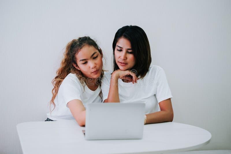 幸福家庭妈妈和十几岁的女儿使用膝上型计算机 免版税库存图片