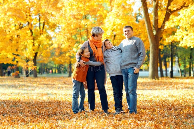 快乐家庭在秋季城市公园里摆姿势玩乐 孩子们和父母一起过得愉快 明亮的阳光 免版税库存图片