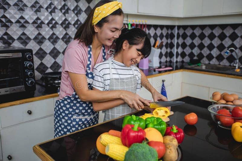 幸福家庭有爸爸、的妈妈和一起烹调他们的小的女儿在厨房 库存图片