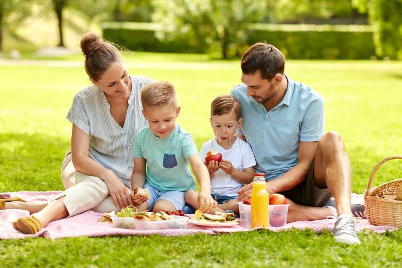 幸福家庭有野餐在夏天公园 免版税图库摄影