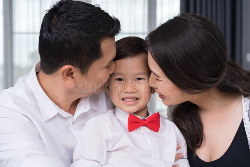 幸福家庭概念、怀孕的亲吻孩子男孩的母亲和父亲 库存图片